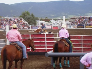 Team ropers watching a bronc rider on opening day.